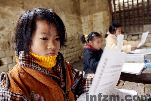 在广西融水苗族自治县泗柳屯教学点,二年级学生王燕娟在复习功课,为明天的期考作准备。