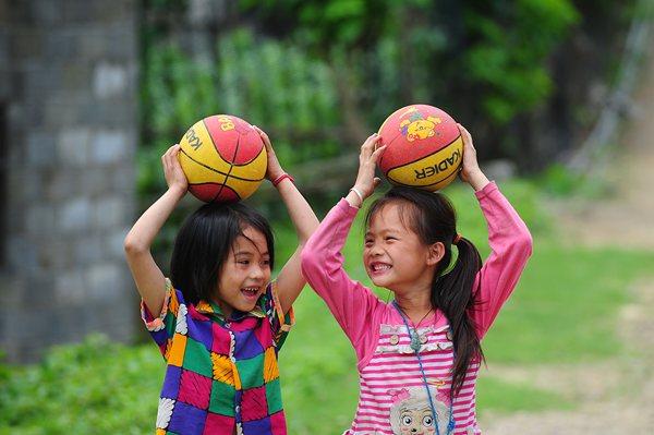 在广西大化瑶族自治县岩滩镇良庆屯教学点,二年级学生唐亿斯(左)和同学唐蕾在玩球(5月17日摄)。