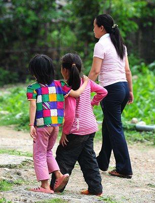 二年级学生唐亿斯(左)、唐蕾和老师准备走进教室。