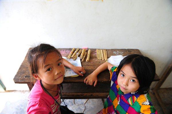 二年级学生唐亿斯(右)和同学唐蕾(左)在利用竹条学习算术。
