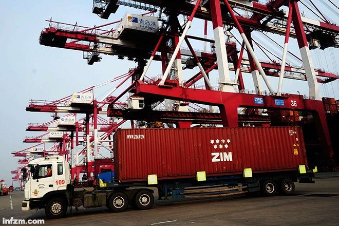 图为2014年2月12日,山东青岛港外贸集装箱码头车辆在运送集装箱.
