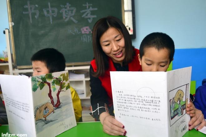 C22.《背诗的可怕经验》(图文无关)2017年3月31日,在山东省聊城市翰林院幼儿园,志愿者在教小朋友学习朗读古诗。