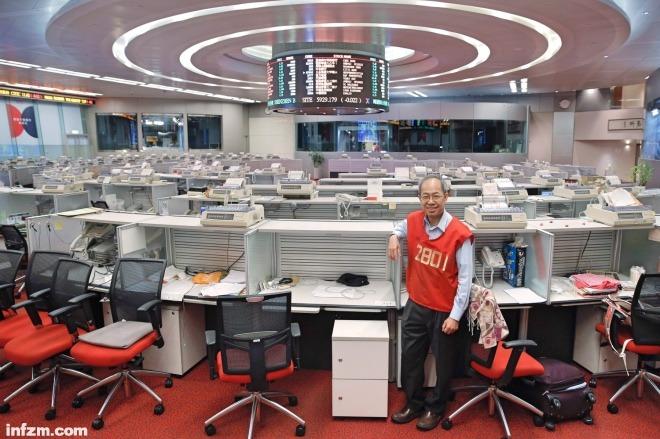 """一名穿着""""红马甲""""的恒丰证券股票经纪在港交所交易大厅拍照留念。"""