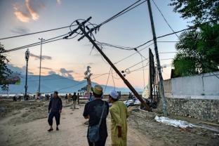当地时间2018年9月29日,印度尼西亚中苏拉威西省首府帕卢市,人们行走在灾后的海滩上。新华社