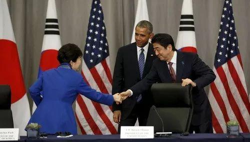 2016年3月31日,时任韩国总统朴槿惠(左)和日本首相安倍晋三(右)在时任美国总统奥巴马(中)的注视下握手。新华社/路透