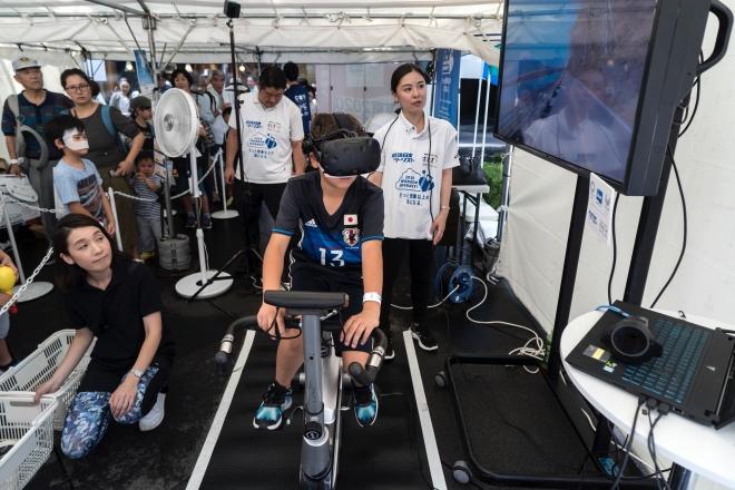 一个男孩头戴VR眼睛骑上健身单车,在2020东京奥运会开幕倒计时一周年的活动上体验虚拟观光。