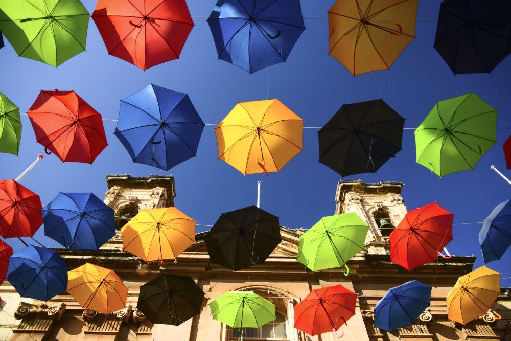 这是7月13日在马耳他扎巴尔街头拍摄的悬挂在空中的雨伞。新华社发(乔纳森·博格摄)