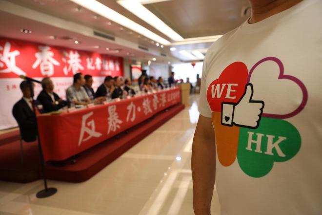 """一位香港市民在""""反暴力·救香港""""的记者招待会上穿着给香港点赞的衣服。"""