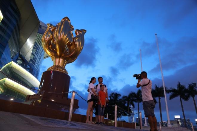 2019年8月15日,晚上7时许,香港金紫荆广场,游客在摄影摊位前拍纪念照。