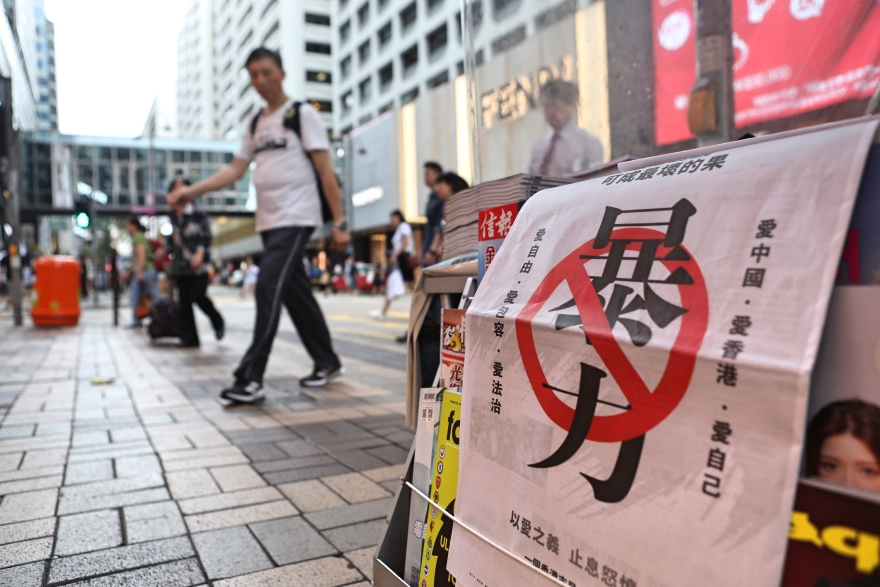 """2019年8月16日,香港街头的报摊摆放了李嘉诚在报纸头版投放的""""反暴力""""广告。"""