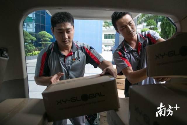 順豐快遞員在把貨物裝車,左一為李濤。