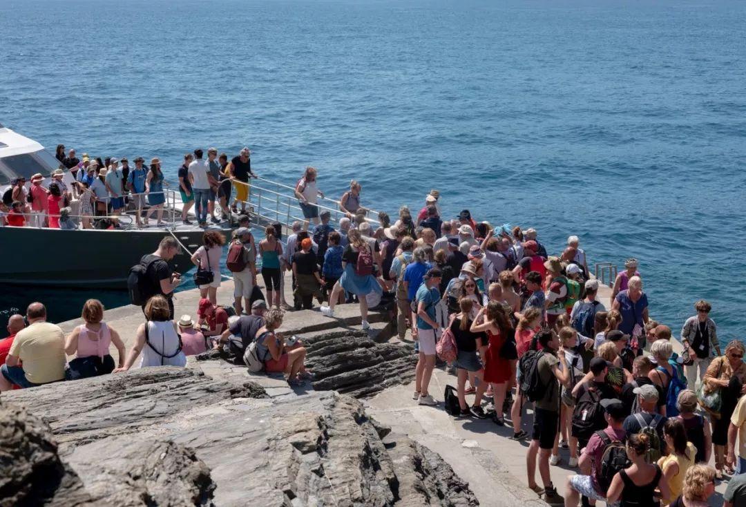 搭乘邮轮的游客登陆,涌向五渔村。