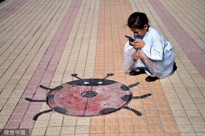 一位小女孩用手机记录下可爱的七星瓢虫井盖。