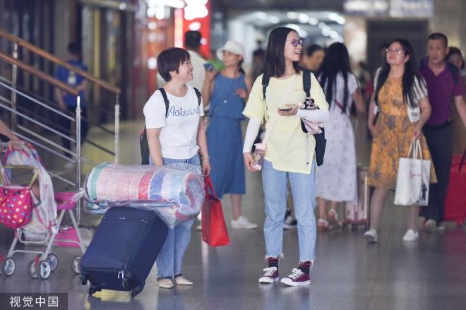 《大学新生报到, 有家长陪是福气》2019年9月6日,武汉各大高校迎来新生报到高峰,高校迎新志愿者们在武昌站举牌迎接来自全国各地的大学新生,欢迎新同学。