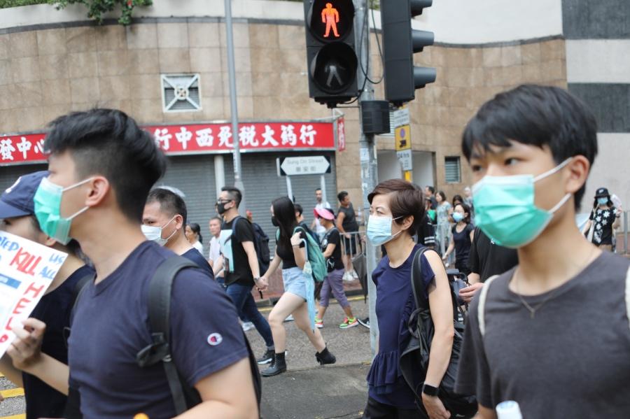 2019年8月17日,在九龙城区的游行示威活动中,参与者戴着口罩参与活动,队伍伍途径的商铺都早早关门。