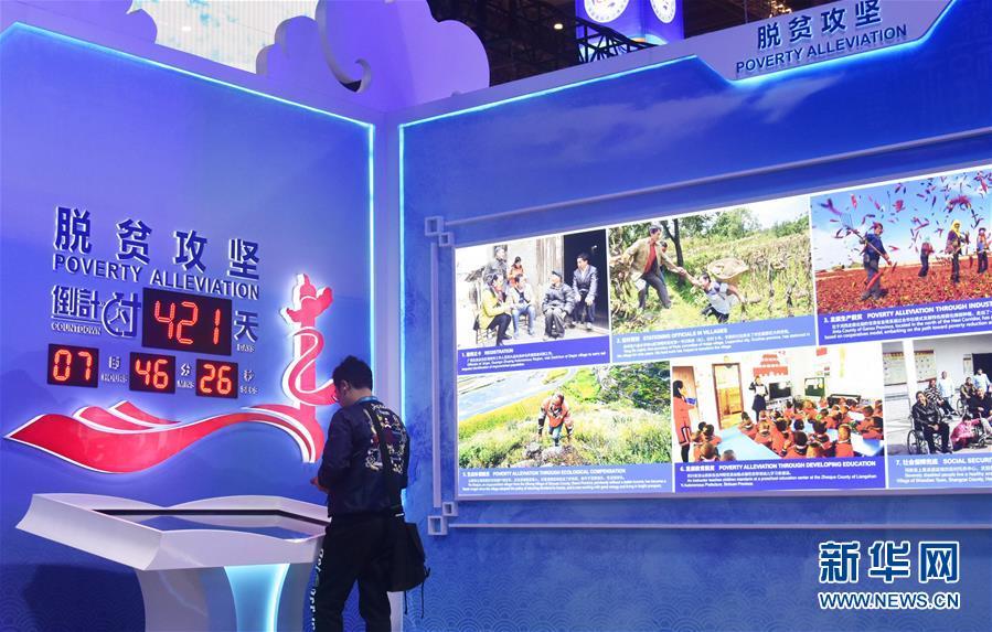 """11月6日,观众在第二届进博会中国馆""""美丽中国""""单元脱贫攻坚倒计时显示屏前参观。 新华社记者 魏海 摄"""