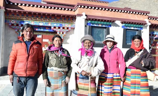 12月23日,西藏那曲市雙湖縣80歲的牧民索朗德慶(中)與親戚在新家門口。