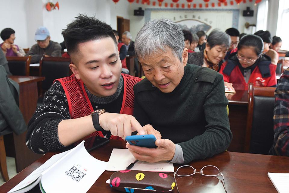 《大家小说 | 父亲的道歉信》(图文无关)志愿者在教老年人使用智能手机。