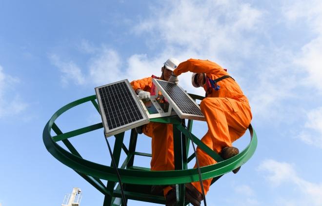 工作人员在海巡172船上为灯浮标安装太阳能电池板。