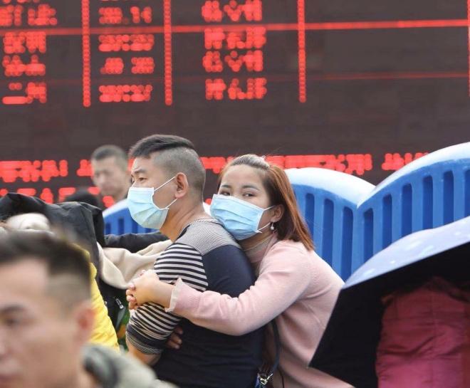 在广州站,两名候车乘客佩戴口罩互相依偎着。