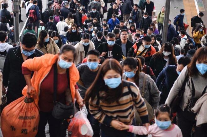 广州南站提着大包小波的乘客,其中大部分人佩戴上了口罩。
