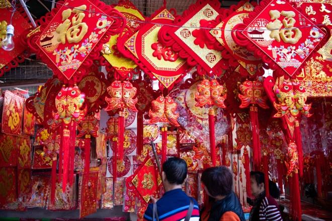 《年味满家国》图为市民在位于澳门佑汉公园的年宵市场购买春联、福字等。