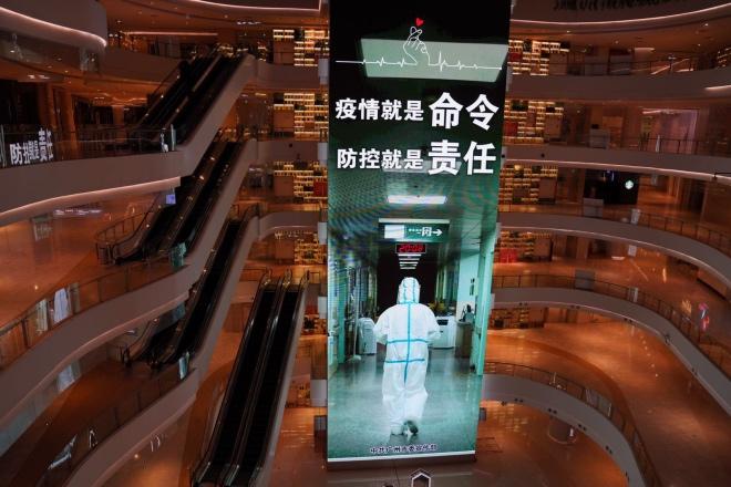 在广州市珠江新城CBD一处商城,只有极少数商家开铺营业。在商城的中庭,一块巨大的LED屏幕在滚动播放防疫广告。