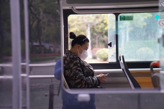 一位市民坐在公交车里玩手机。抗击新冠肺炎疫情期间,为了通风透气,广州市的公交车基本上都把车窗打开行驶。