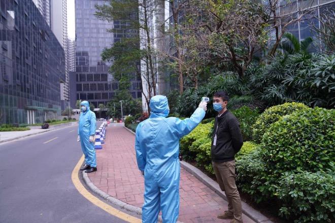 珠江新城某写字楼,工作人员全副武装,为进入写字楼的人群测量体温。