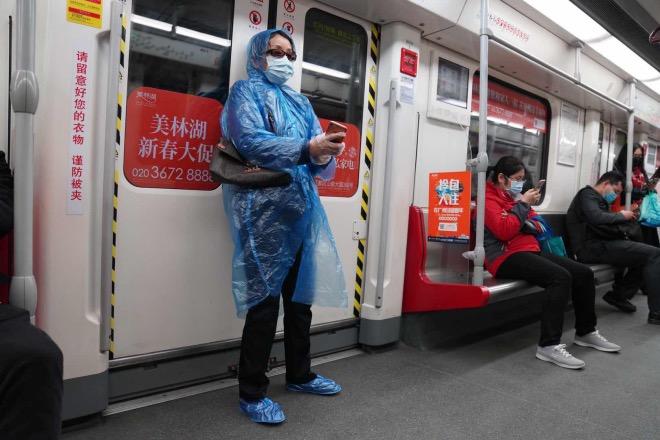 地铁三号线列车上,市民各出奇招加强防护,有人披雨衣穿鞋套。