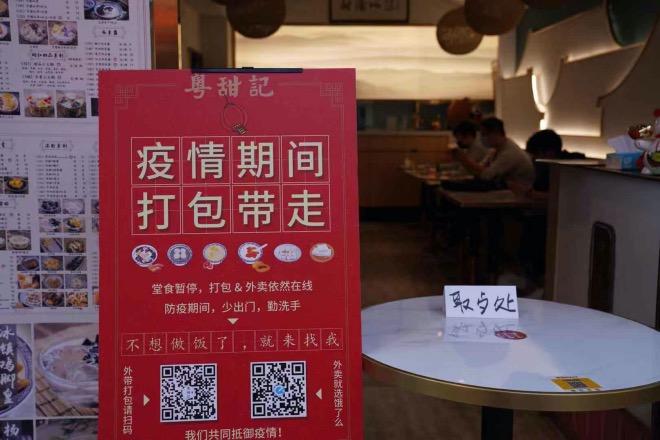 一個餐飲商家把一張餐桌攔在店門口,用來放客戶訂的餐食,避免雙手接觸。