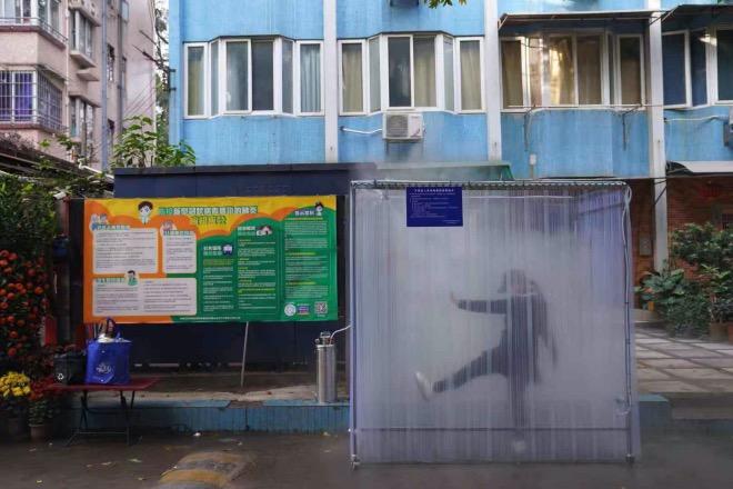 """为了达到更好的消毒效果,小区居民在消毒通道里""""手舞足蹈"""",增加干喷雾的接触面积。"""