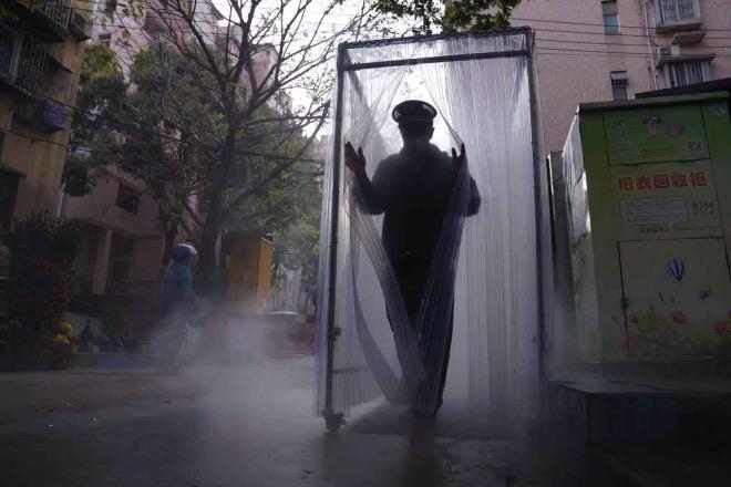 物管安保人员平时接触的人数比较多,是被病毒传播的高危群体。图为一名保安员在使用消毒通道。