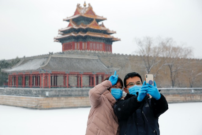 """2020年2月5日,北京,一场春雪,一些在家里憋得难受的市民还是戴着口罩出来到故宫角楼赏雪。""""一下雪,北京就成了北平。""""但此时,这雪景也没有那么浪漫了。"""