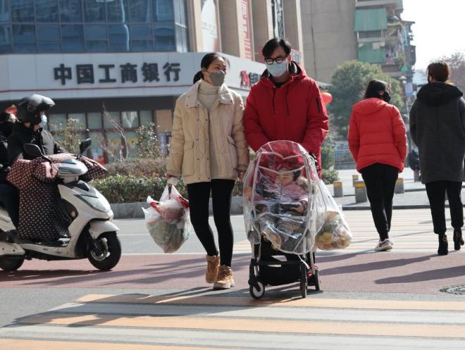 農歷庚子鼠年正月初五(2020年1月29日),湖北宜昌。春節假期被突然延長,不少人上街補充食物。一對夫妻購物后推著密閉的嬰兒車回家。