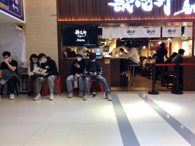 在一家日本風味餐廳外等座的人。