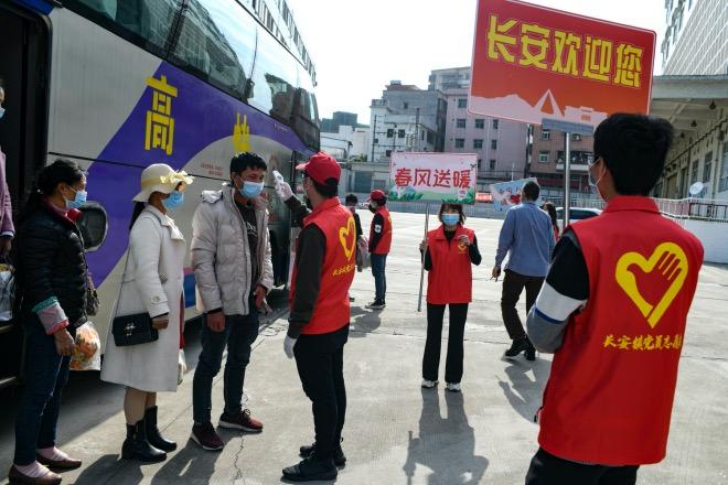 2020年2月23日,廣東東莞,企業包車將云南文山州的員工接回工廠。志愿者給他們測量體溫。