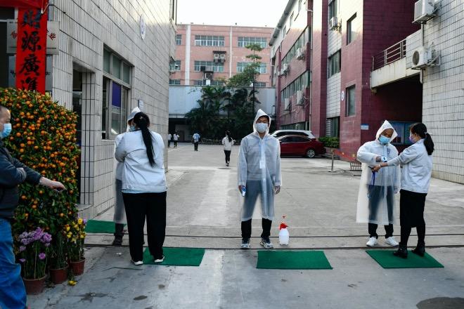 2020年2月22日,廣東東莞,工廠門口的檢測人員穿著一次性雨衣當防護服。