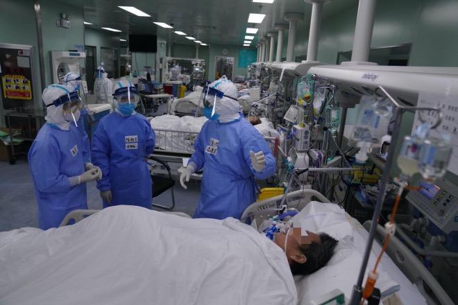 廣東支援湖北疫情防控醫療隊的幾位醫生在商量治療病人采用的方法。
