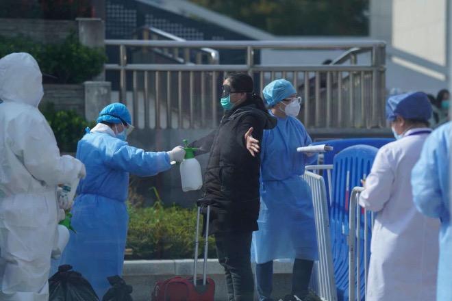 武昌方艙醫院最后一批病人出院。病人出艙后要進行全身消毒。