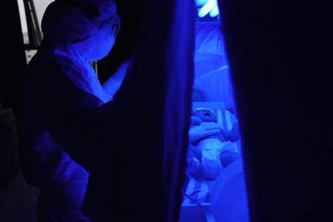 蔡慧護士在安撫一個哭泣的感染了新型冠狀病毒肺炎的嬰兒。
