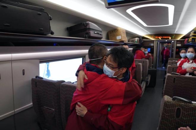 第二批广东医疗队队长张忠德和返穗的队友相拥告别。他和另外72名中医队医护人员继续留守在雷神山医院救治病人,归期未定。