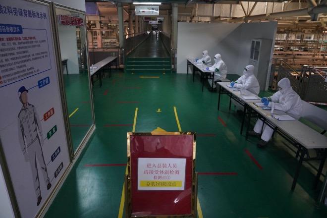 總裝車間前的防疫點。每一位進入工廠的工作人員,必須先經過嚴格的體溫檢查和酒精噴灑式的病毒消殺,防疫、復工兩不誤。