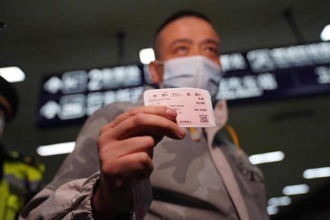 3月28日,武昌火車站出站口,一位從河南信陽經湖北孝感中轉的乘客回到武漢,他展示手里的車票。