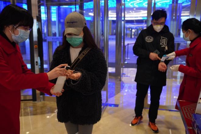 """武漢國際廣場購物中心是武漢大型商場之一。顧客進入商場需要出示""""綠碼""""、通過紅外線測溫儀,測完溫后,工作人員會遞上消毒液,示意顧客洗手。"""