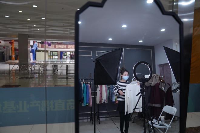 因为疫情期间实体店没有顾客,汉口北批发市场的店主支起手机开始网上直播卖货。2