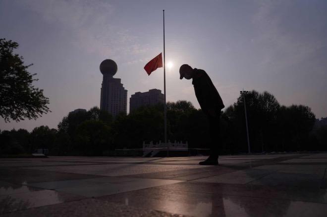 武漢市民面朝漢口江灘的國旗,鞠躬默哀。