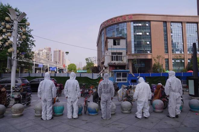 武汉市中心医院门口,身着防护员的保安人员在默哀。