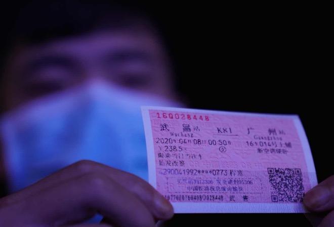 一位乘客展示始发站武昌、终到站广州的车票。