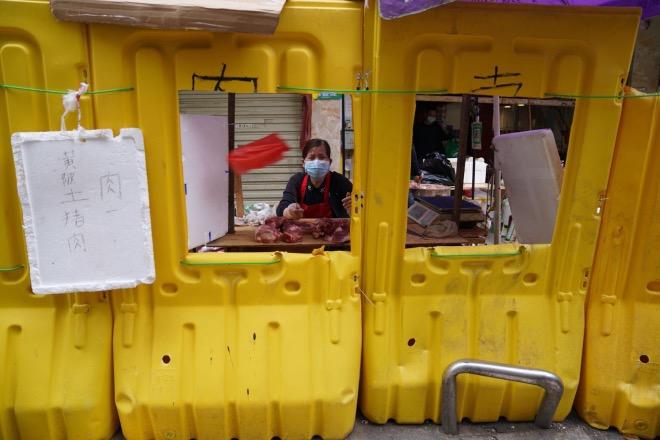 汉口民主一街的社区隔离带的围栏上有几个洞,方便人们过来买菜。